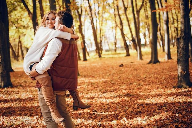 Элегантная пара в солнечном осеннем парке