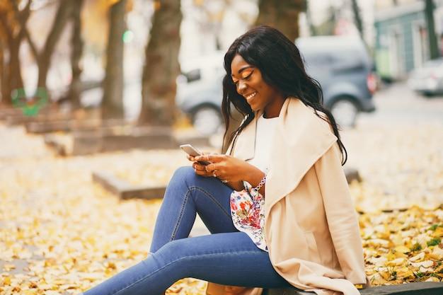 秋の街に座っている黒人女性