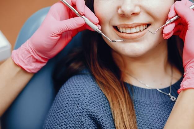 Красивая девушка сидит в кабинете стоматолога