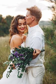 夏の畑で美しい結婚式のカップル