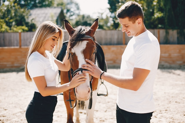 Красивая пара проводит время с лошадьми