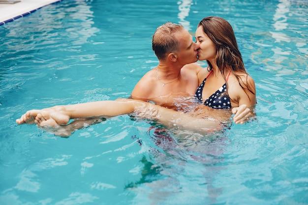 エレガントなカップルはプールで泳ぐ