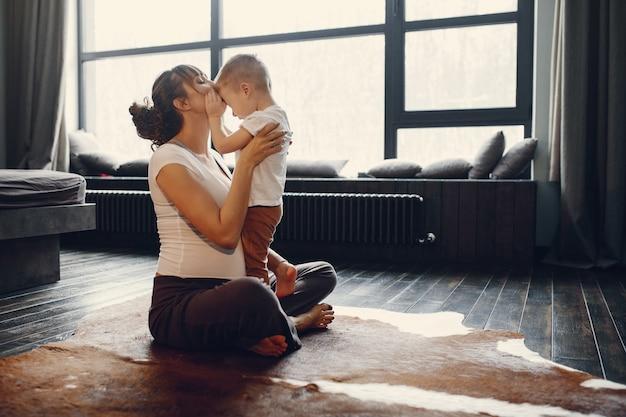家でヨガをやっている幼い息子を持つ母