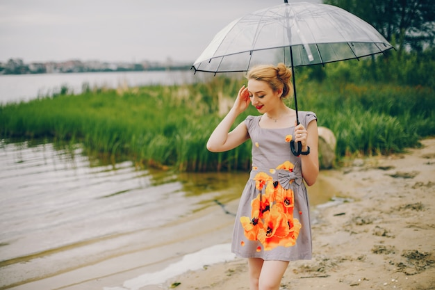 Молодая и красивая девушка в летнем парке