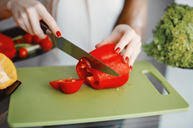 美しい女性は台所で食べ物を準備します。