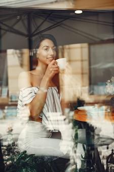 夏のカフェでファッションの若い女の子