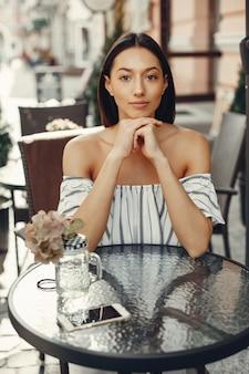 Модная молодая девушка в летнем кафе