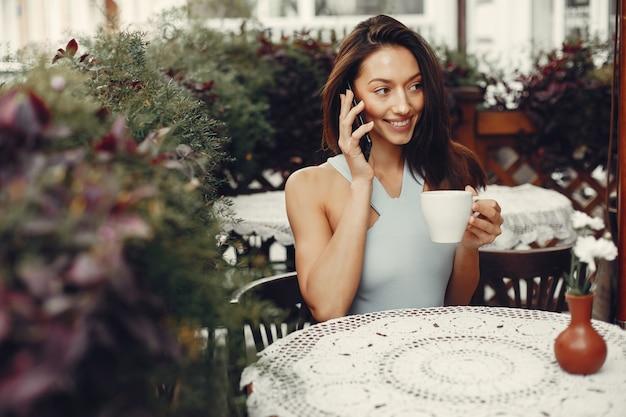 ファッションの女の子がカフェでコーヒーを飲む