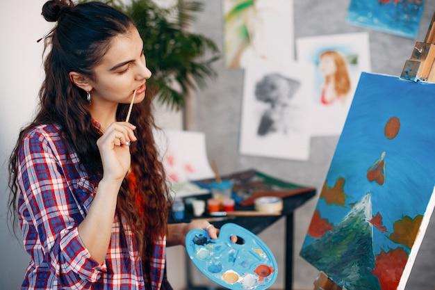 エレガントな女の子がアートスタジオで描く
