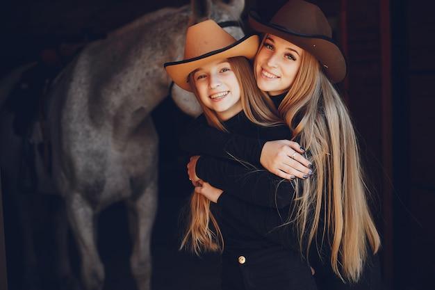 牧場で馬を持つエレガントな女の子