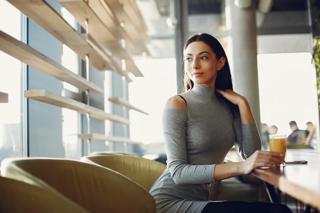 カフェに座っているファッションの若い女の子