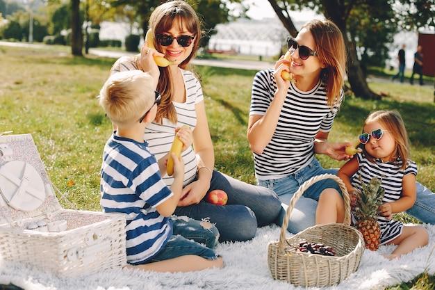 夏の公園で遊ぶ子供たちと母親