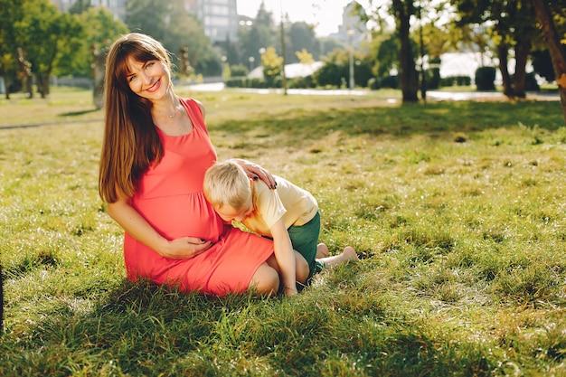 夏の公園で遊ぶ子供を持つ母