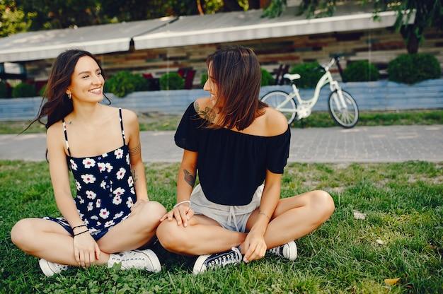 Стильные девушки гуляют в летнем парке