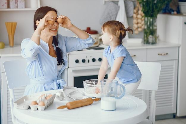 かわいい家族が台所で朝食を準備します。