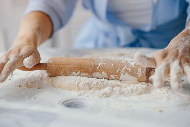 美しい女性はクッキーの生地を調理する