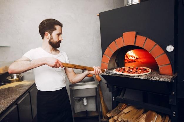 台所でシェフがピザを準備