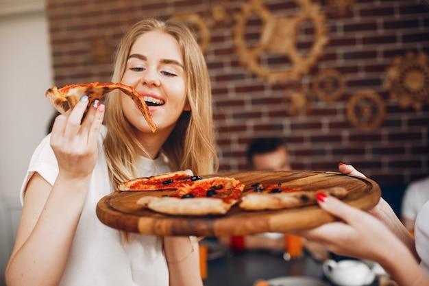 Милые друзья в кафе, едят пиццу
