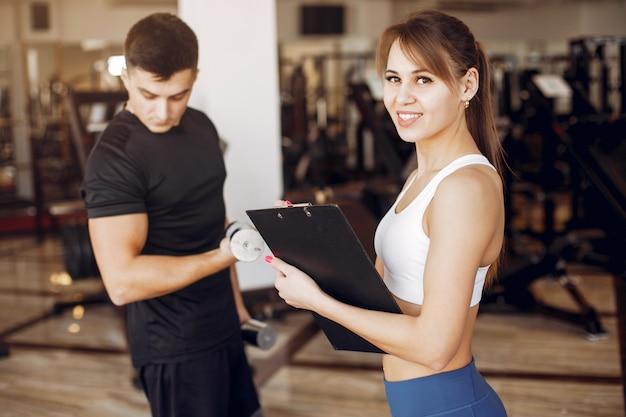 美しいスポーツカップルはジムで従事しています。