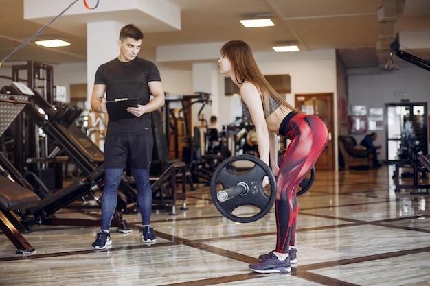 Красивая спортивная пара занимается в тренажерном зале