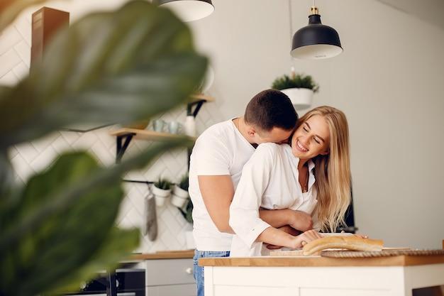 美しいカップルは台所で食べ物を準備します