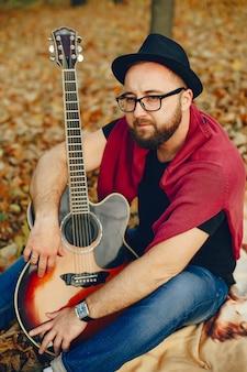 秋の公園で座っているハンサムな男