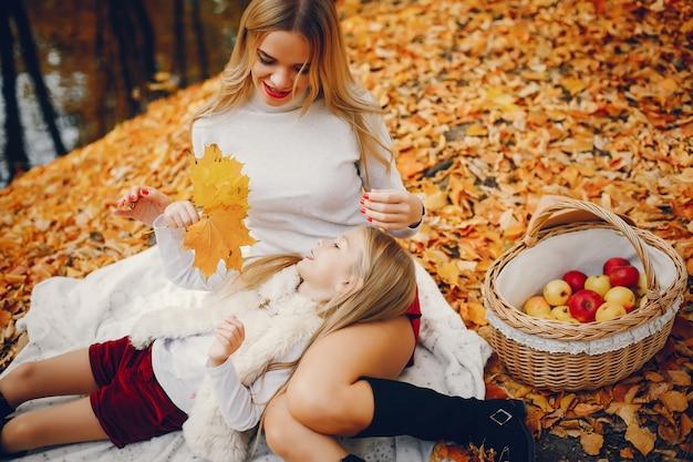 秋の公園でかわいい、スタイリッシュな家族