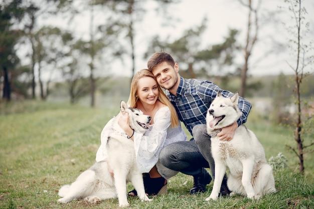 Красивая пара в летнем лесу с собаками
