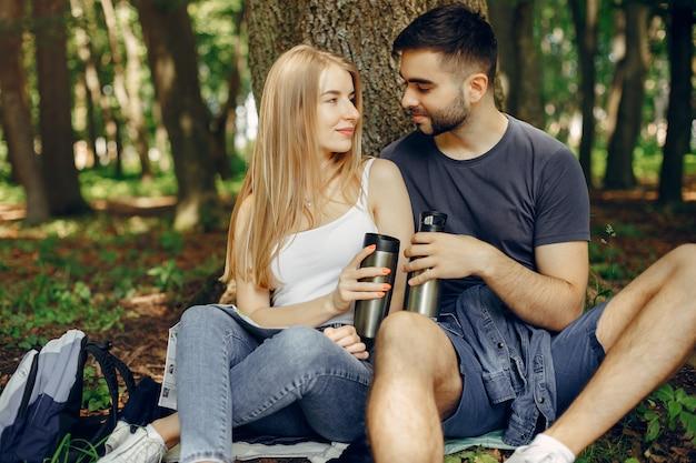 かわいいカップルは夏の森で休憩