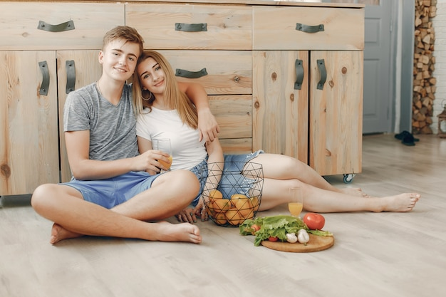 美しいカップルは、キッチンで食事を準備します