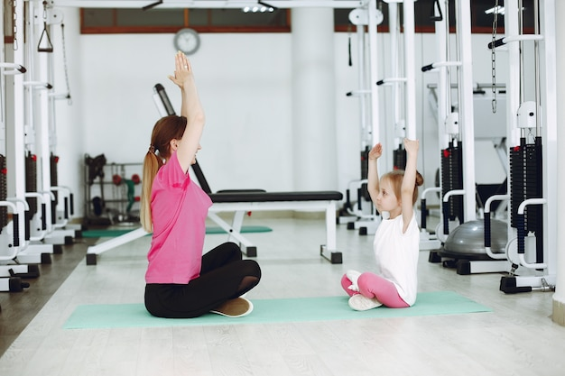 小さな娘を持つ母は、ジムで体操に取り組んでいます