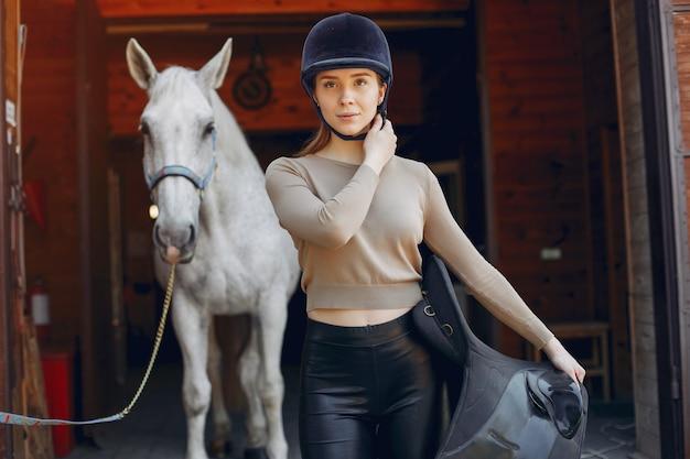 Красивая женщина, стоящая с лошадью