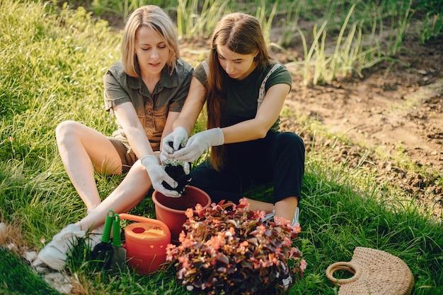 Мама с дочкой работает в саду возле дома