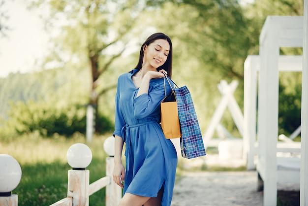 公園で買い物袋を持つかわいい女の子