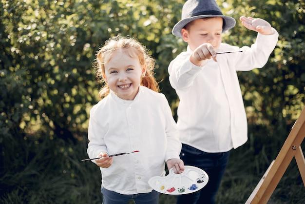 Симпатичные маленькие дети рисуют в парке