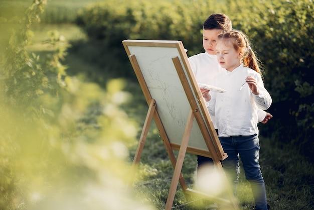 かわいい小さな子供たちが公園で絵を描く