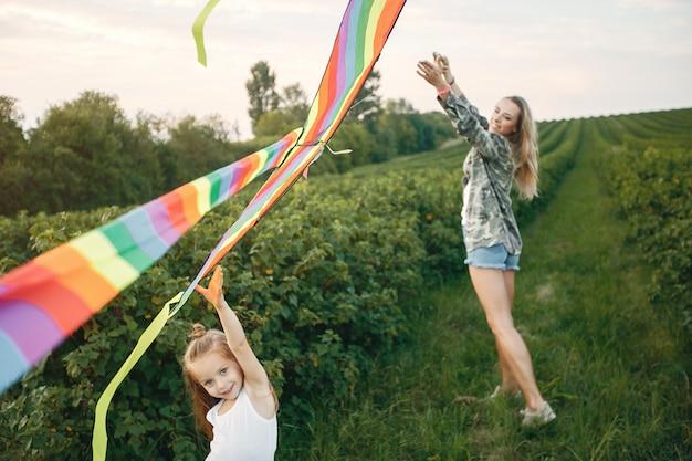 夏の畑でかわいい小さな娘を持つ母
