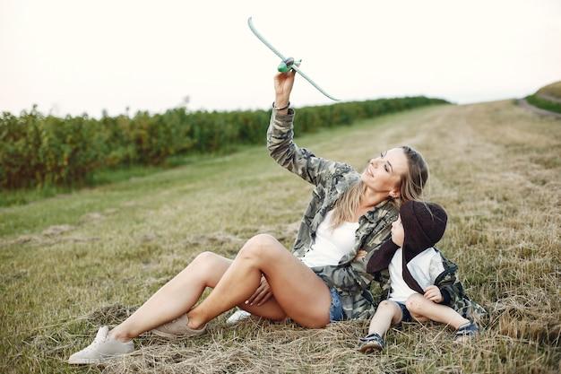 夏の畑でかわいい幼い息子を持つ母