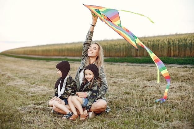 夏の畑でかわいい小さな子供を持つ母
