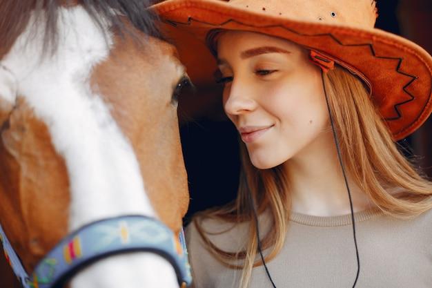 馬と立っている美しい女性
