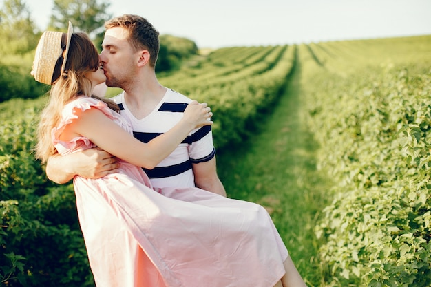 美しいカップルが夏の畑で時間を過ごす