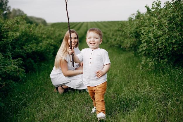 Мать с сыном играет в летнем поле