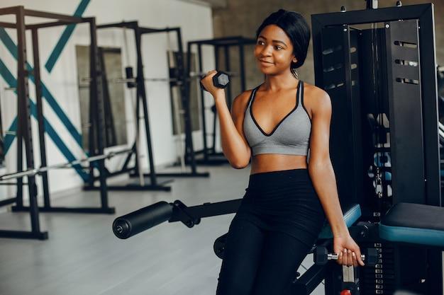 Красивая черная девушка занимается в тренажерном зале