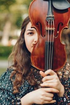 ヴァイオリンと夏の公園で美しい少女