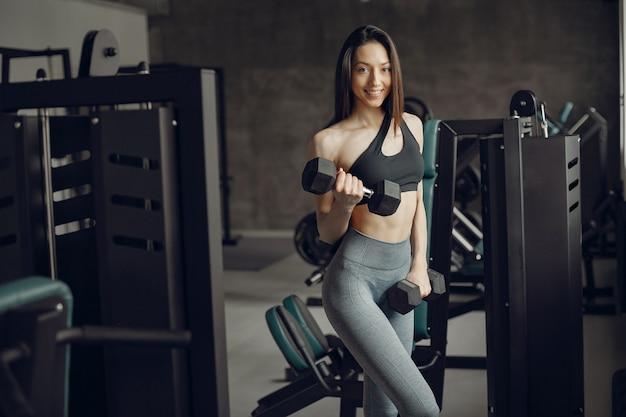 Красивая девушка занимается в тренажерном зале