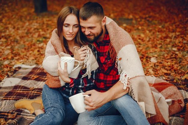 秋の公園で時間を過ごすエレガントなカップル