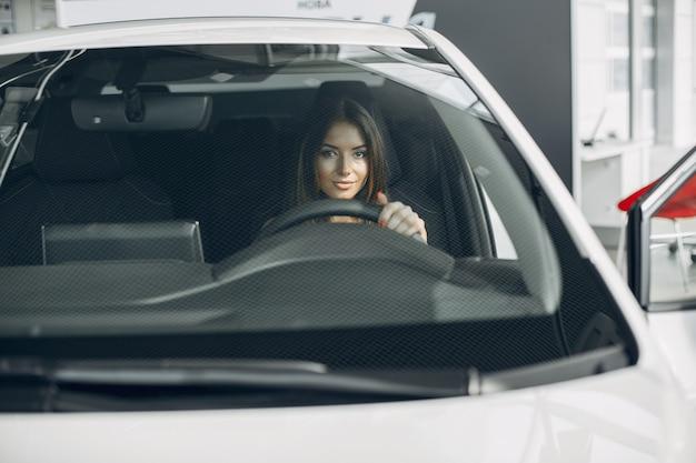 車のサロンでスタイリッシュでエレガントな女性