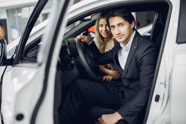 車のサロンでスタイリッシュでエレガントなカップル