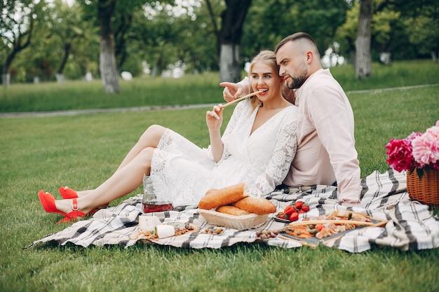 美しいカップルは夏の庭で時間を過ごす