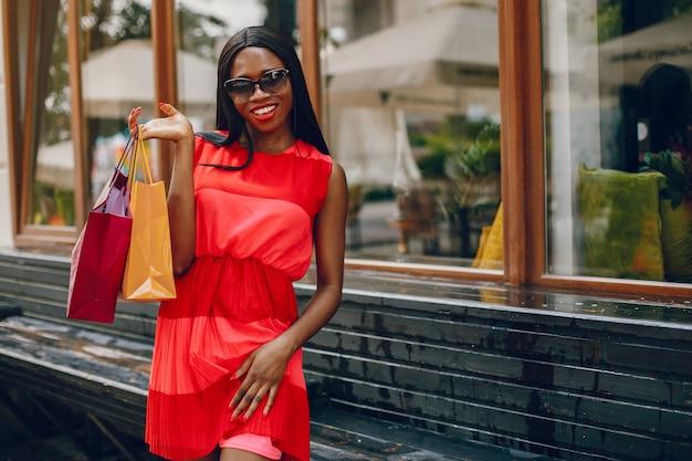 Красивая черная девушка с сумками в городе